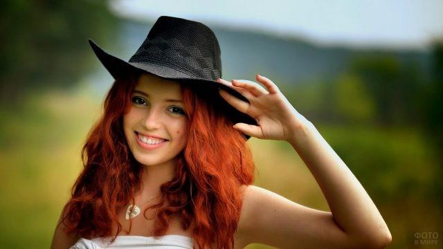 Улыбающаяся девушка в чёрной шляпе на природе
