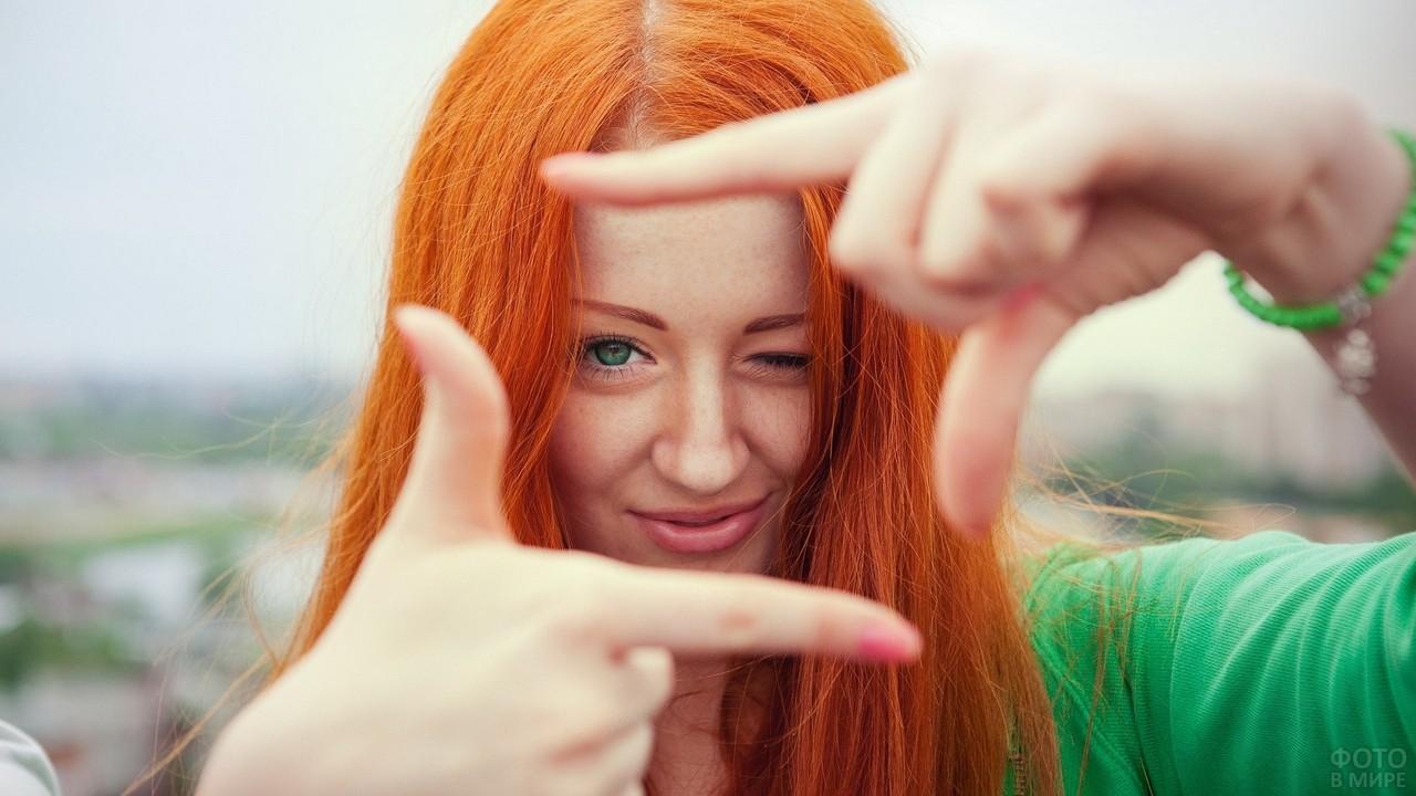Весёлая девушка подмигивает сквозь пальцы