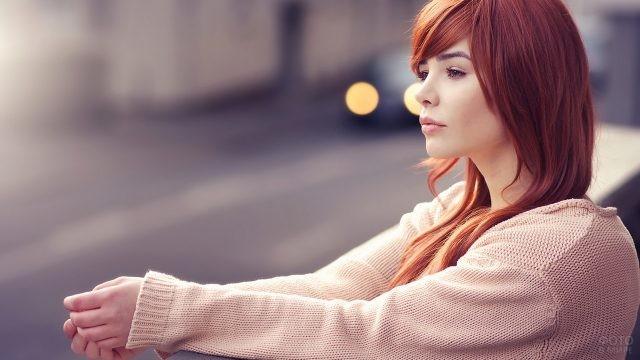 Задумчивая девушка в розовом вязаном кардигане