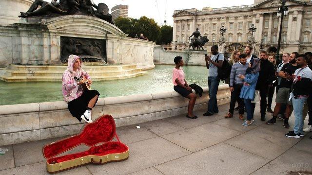 Уличный музыкант и туристы у памятника королеве Виктории