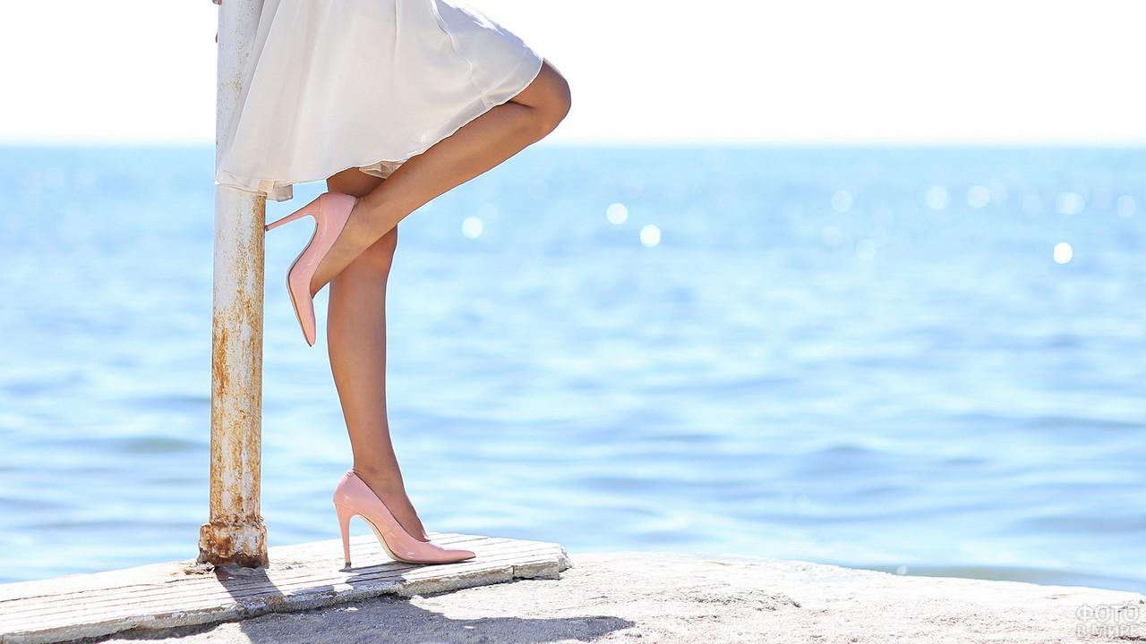 Девушка подняла одну ногу у моря