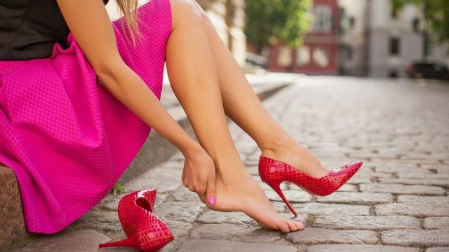 Девушка сняла туфлю на бордюре