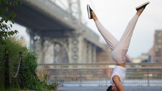Девушка стоит на голове у моста