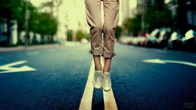 Девушка в кедах прыгает на шоссе