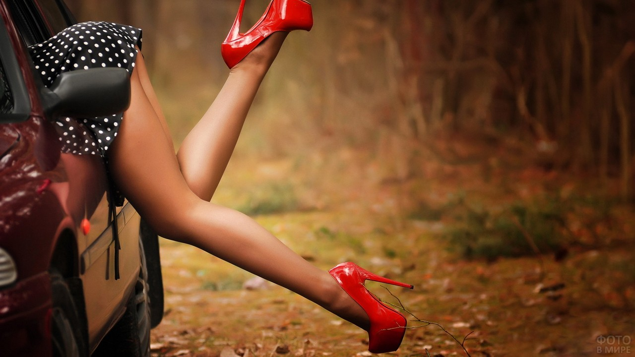 Девушка в красных туфлях в машине