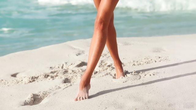 Ноги девушки на песке у моря