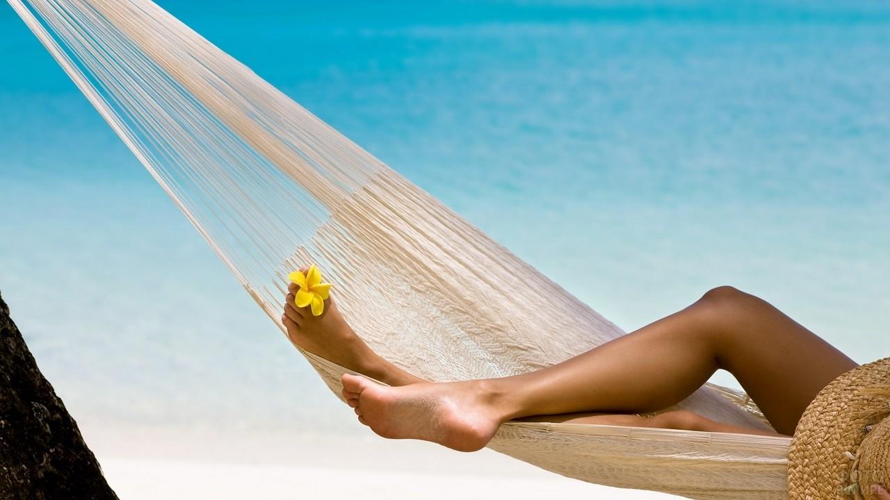 Отдыхающая девушка в гамаке у моря