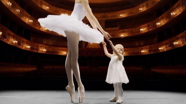 Девочка держит за руки балерину