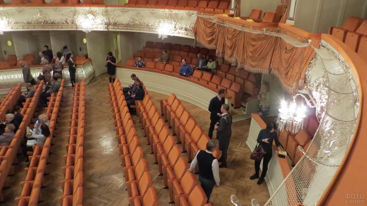 Люди собираются в зрительном зале