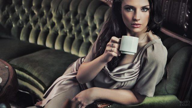 Яркая девушка пьёт кофе на софе