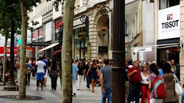 Люди, прогуливающиеся вдоль бутиков и кафе