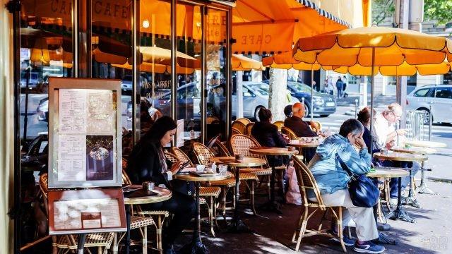 Отдыхающие за столиками уличного кафе