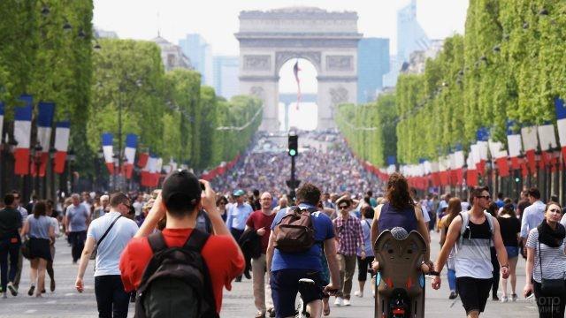 Пешеходы на праздничной Шанз-Элизе у Триумфальной Арки
