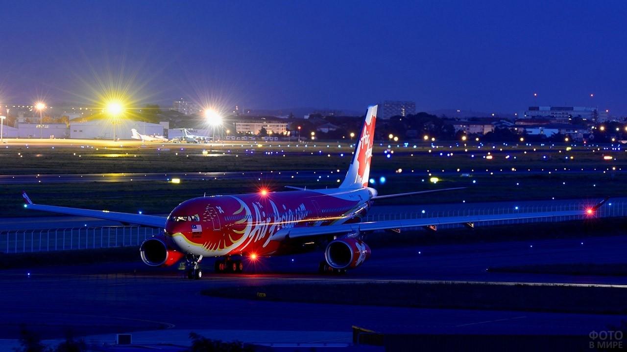 Красочный пассажирский лайнер среди вечерних огней ВПП