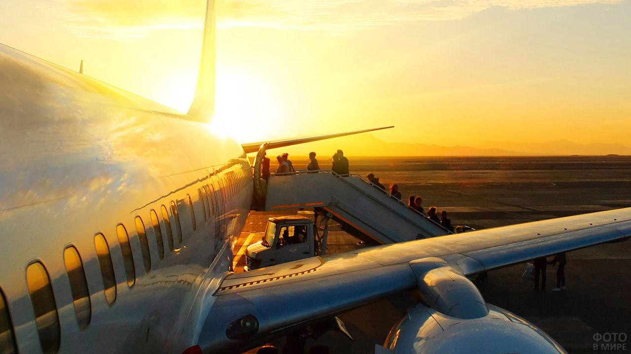 Пассажиры поднимаются по трапу на фоне заката