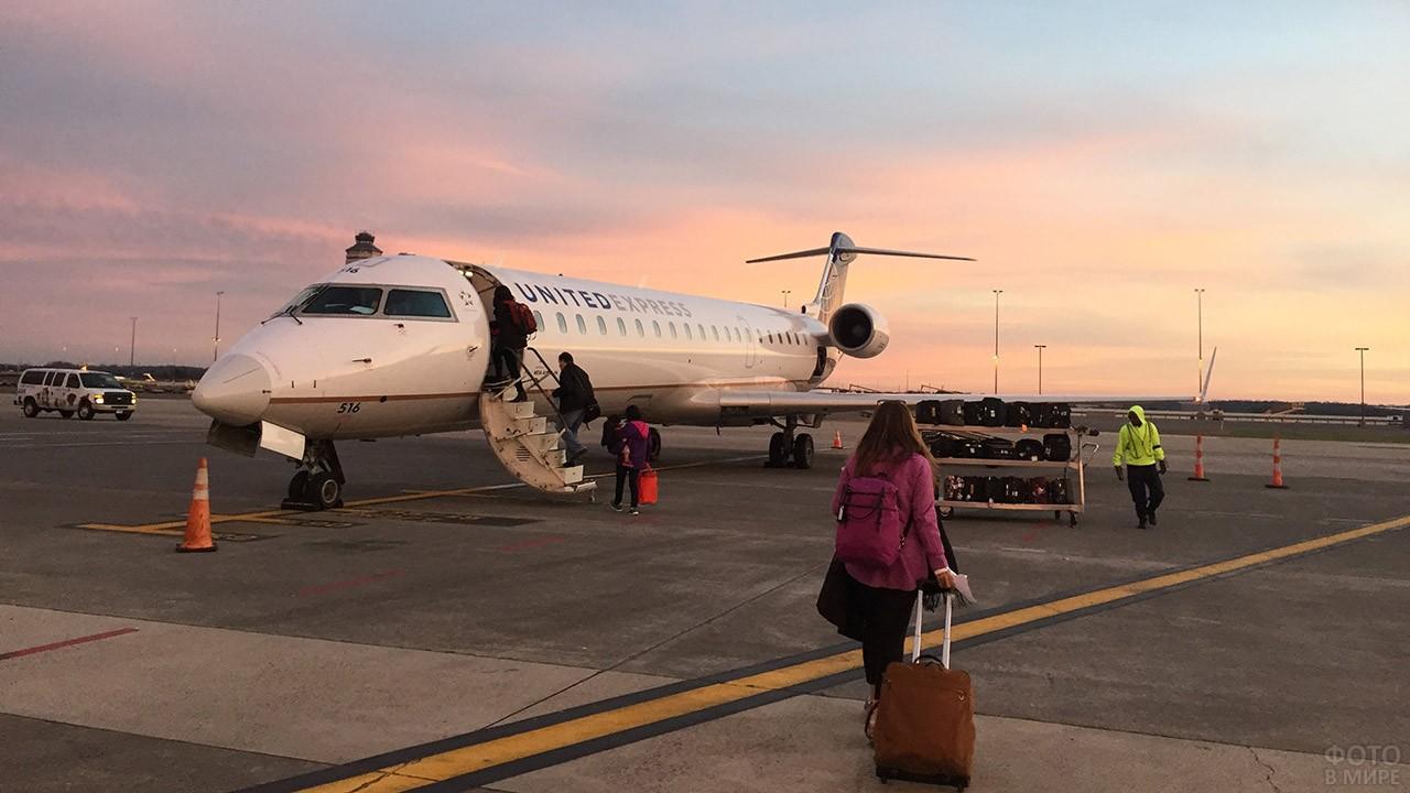 Туристка с чемоданом идёт к трапу самолёта