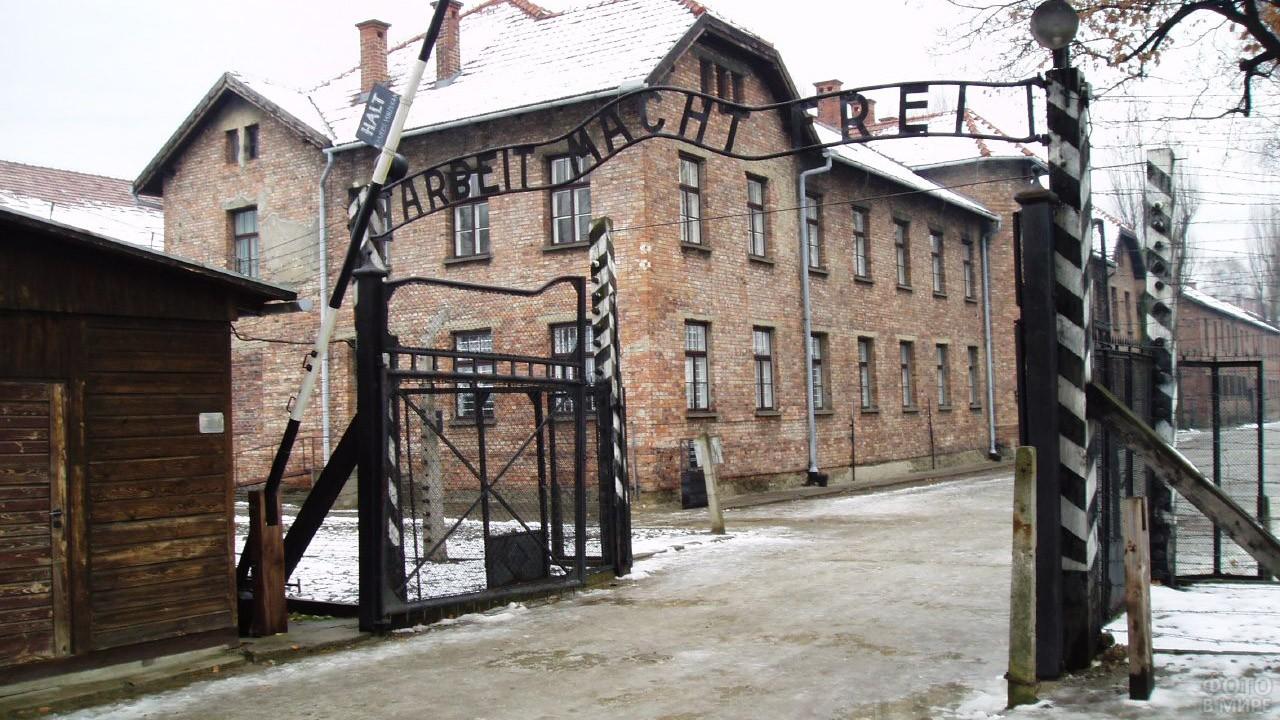 Ворота с шлагбаумом на припорошенной снегом дороге в лагерь смерти