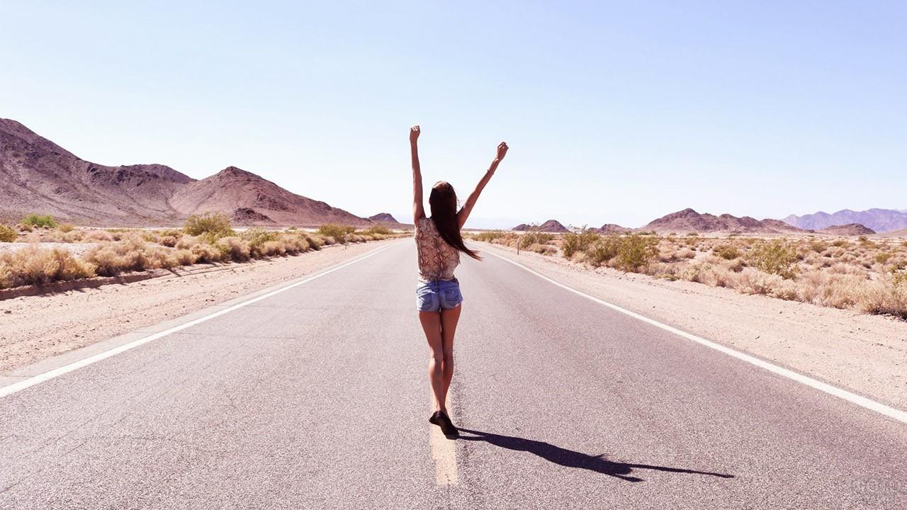 Девушка танцует на пустынной дороге