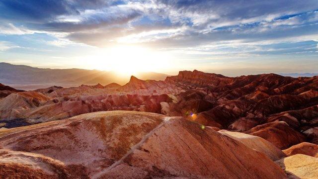 Лучи восходящего солнца над горной грядой