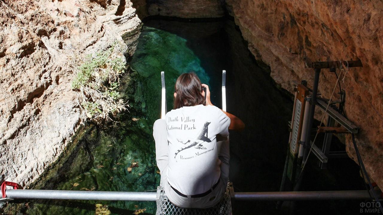 Турист фотографирует воду на дне карстовой пещеры Яма Дьявола