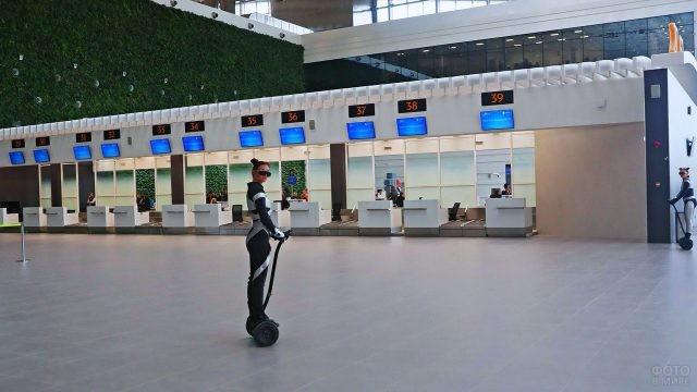 Девушка-промоутер на гироскутере в зале регистрации пассажиров