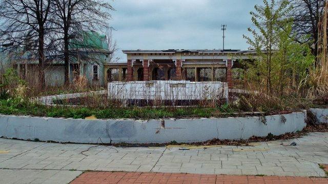 Фонтан на фоне заброшенных зданий