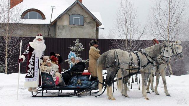 Дед Мороз и Снегурочка с малышами и их бабушкой в санях, запряжённых тройкой