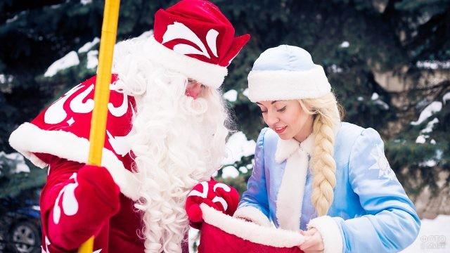Дед Мороз и Снегурочка смотрят в мешок с новогодними подарками
