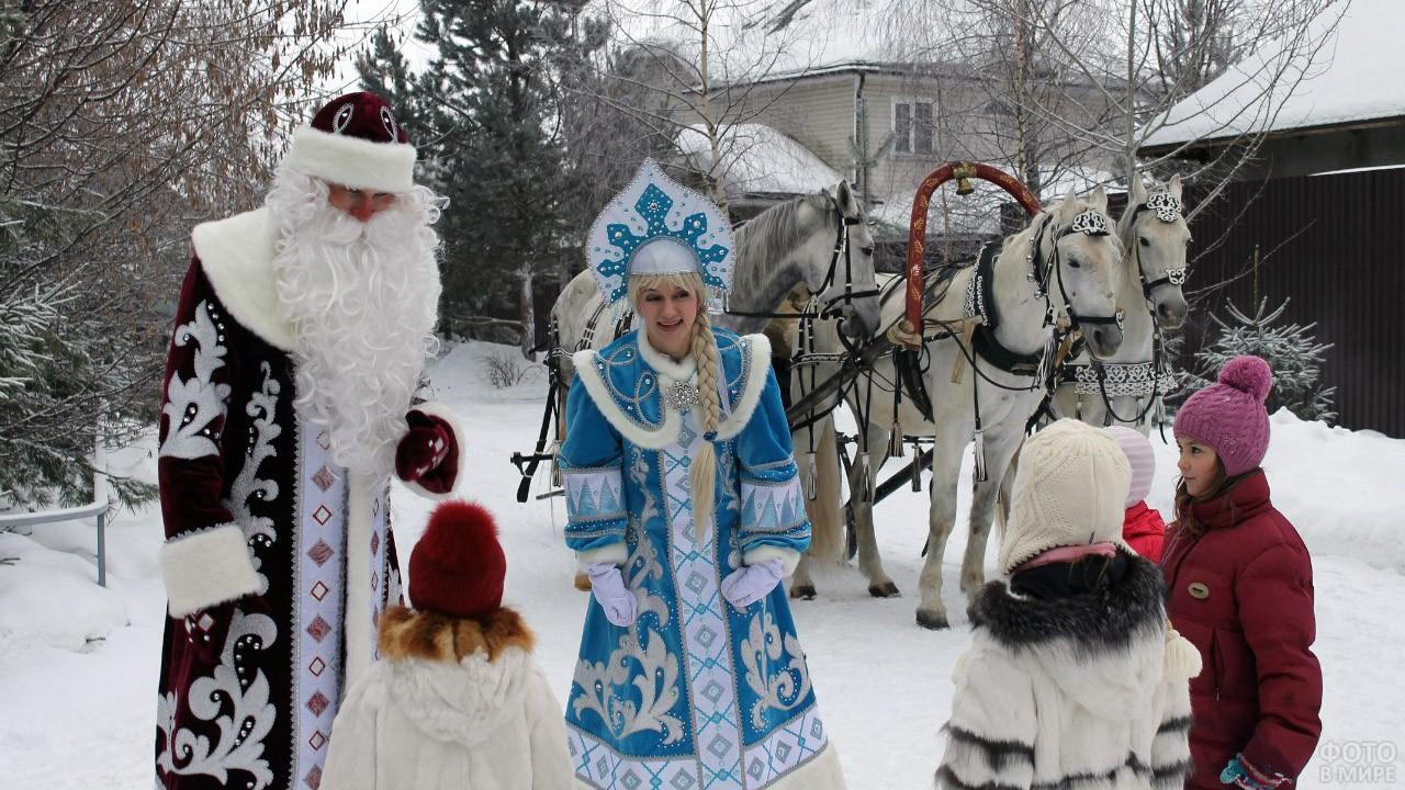 Дед Мороз и Снегурочка среди малышей у тройки белых коней во дворе дома