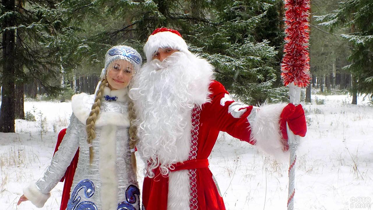 Дед Мороз и Снегурочка среди заснеженных елей