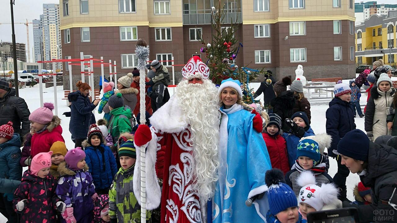 Дед Мороз и Снегурочка стоят обнявшись в толпе детей во дворе многоквартирного дома