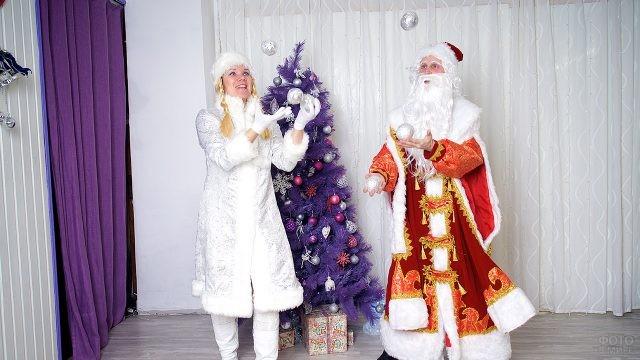 Дед Мороз и Снегурочка жонглируют ёлочными игрушками