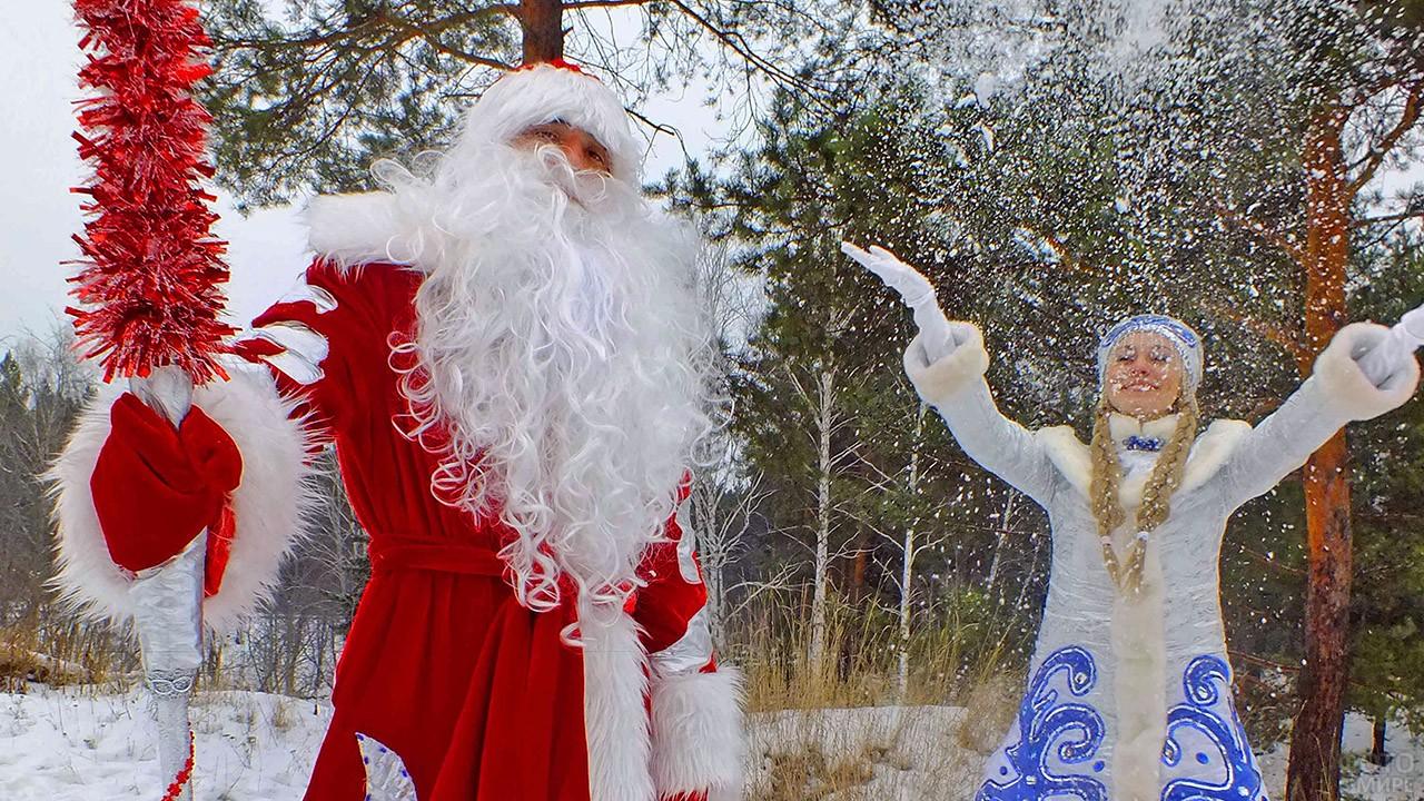 Дед Мороз на фоне Снегурочки подкидывающей над головой снег