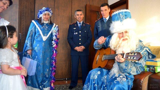 Дед Мороз с гитарой и Снегурочка в компании офицеров МВД поздравляют детей коллег