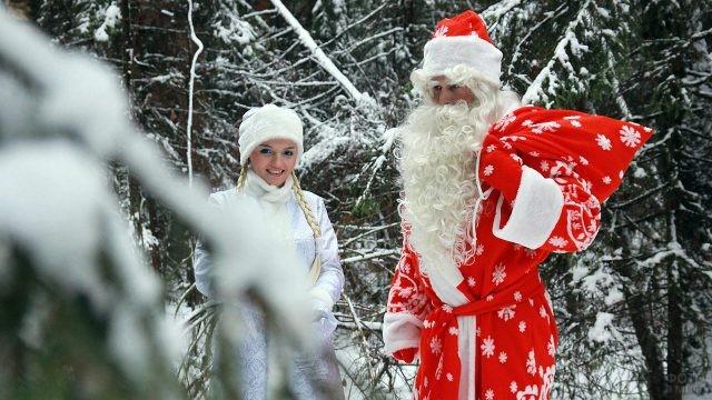 Дед Мороз с мешком подарков и юная Снегурочка в зимнем лесу