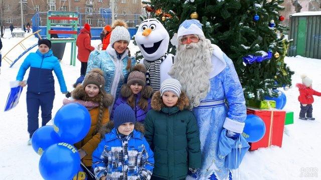 Дед Мороз со Снегурочкой и снеговик из мультика с малышами во дворе многоквартирного дома