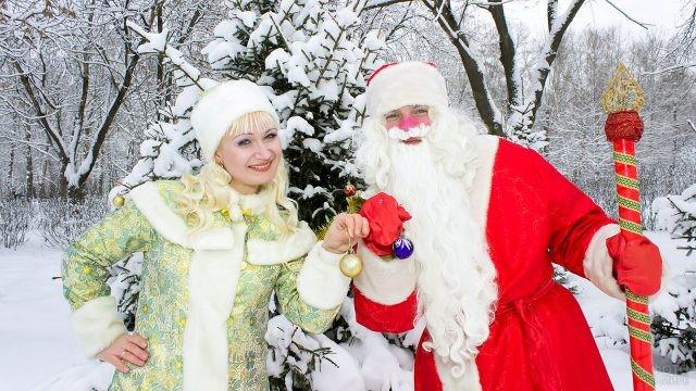 Дед Мороз со Снегурочкой с ёлочными шариками в руках на фоне зимнего леса