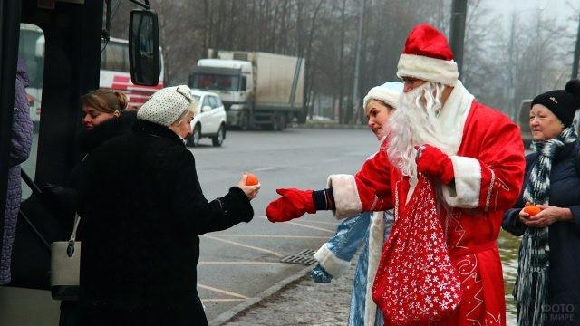 Дед Мороз со Снегурочкой угощают пенсионеров мандаринами на автобусной остановке
