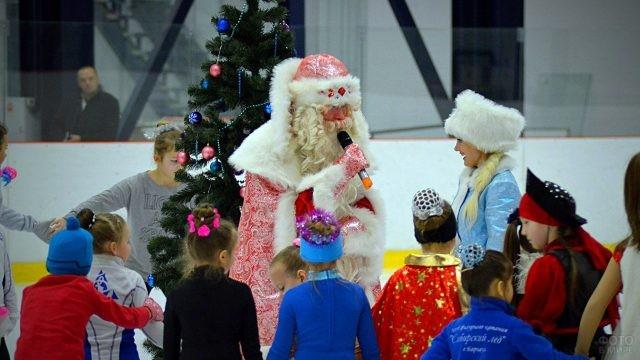 Дед Мороз со Снегурочкой ведут детский праздник на катке