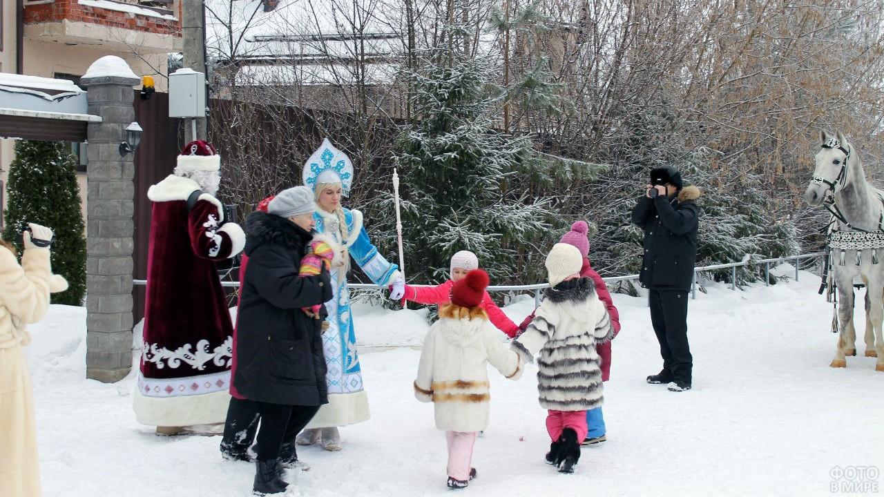 Дед Мороз со Снегурочкой водят с ребятишками и их бабушкой хоровод во дворе загородного дома