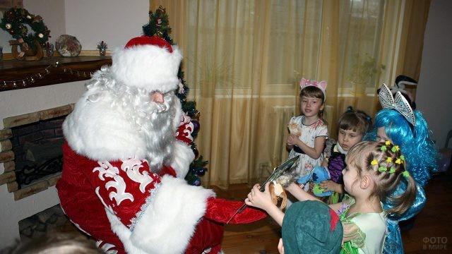 Дедушка Мороз раздаёт малышам подарки