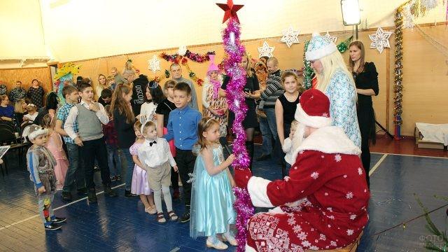 Дети на утреннике подходят к Деду Морозу за подарками