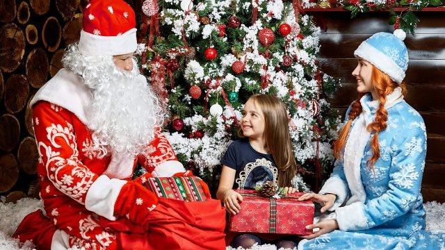 Девочка получает подарок под новогодней ёлкой