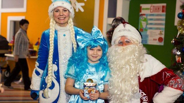 Девочка в костюме Мальвины с Дедом Морозом и Снегурочкой