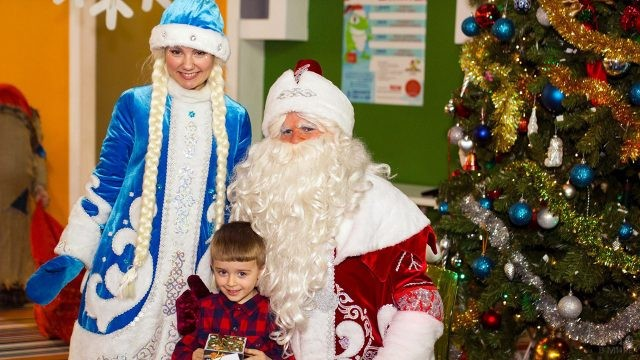 Довольный малыш с Дедом Морозом и Снегурочкой под нарядной ёлкой