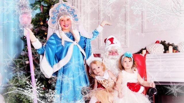 Две нарядных малышки и Дед Мороз со Снегурочкой у ёлки у камина