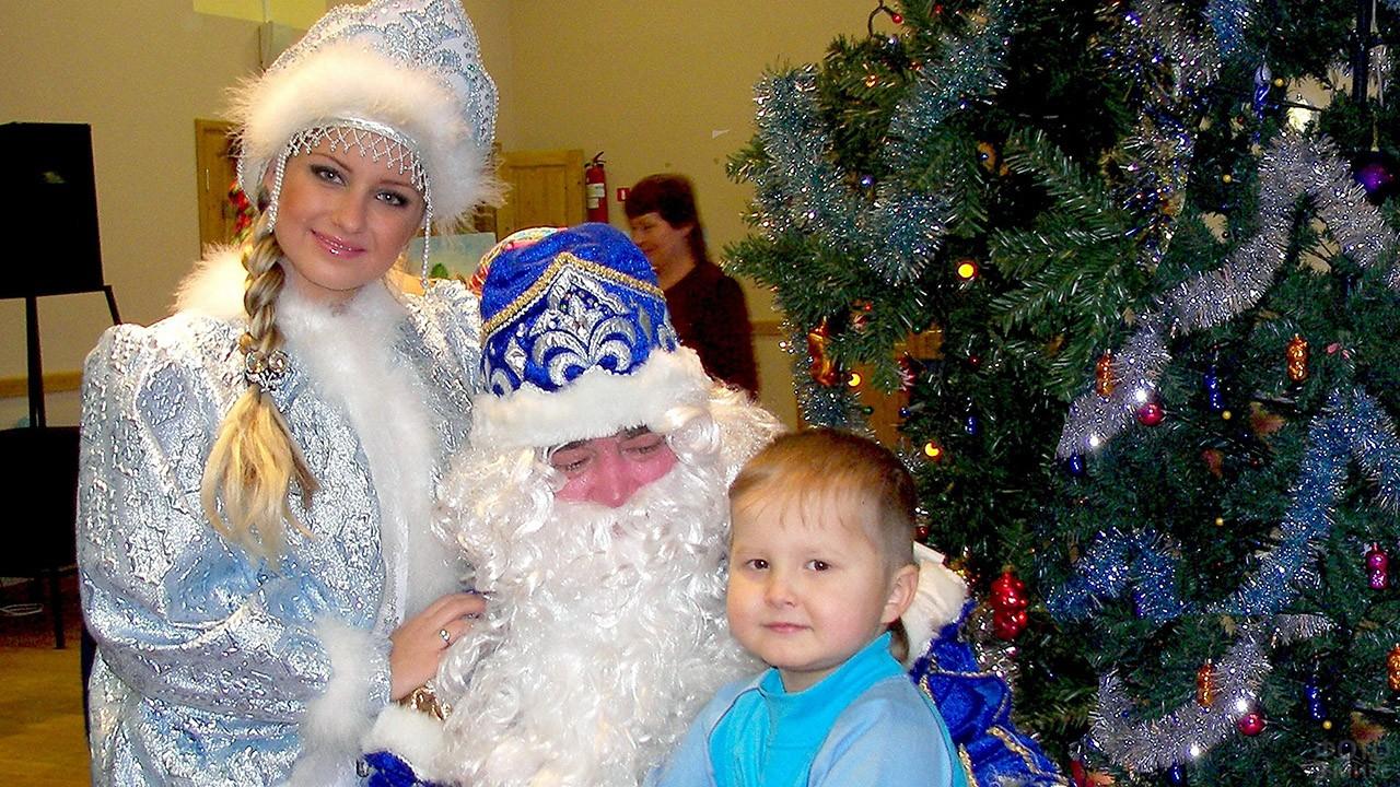 Мальчик на коленях у Деда Мороза и Снегурочка рядом с ёлкой