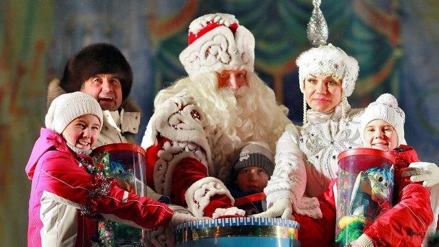 Счастливые дети с подарками и их отец вокруг Деда Мороза и Снегурочки