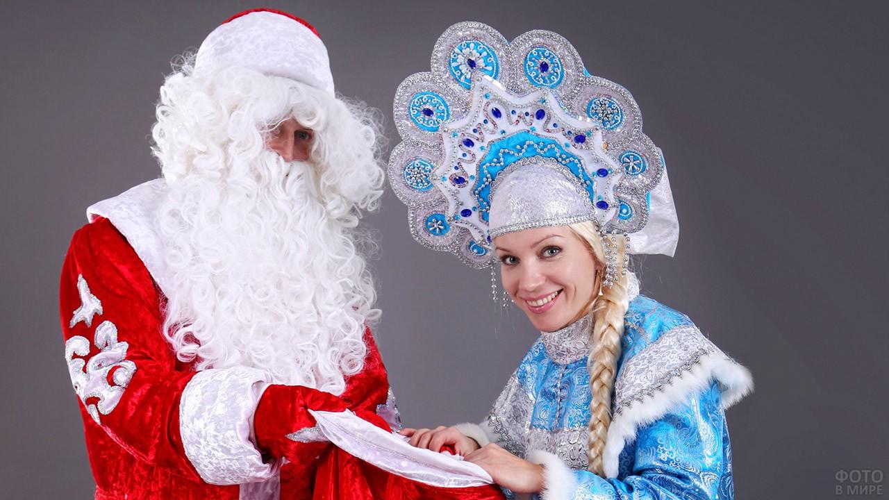 Снегурочка в нарядном кокошнике заглядывает в мешок с подарками Деда Мороза