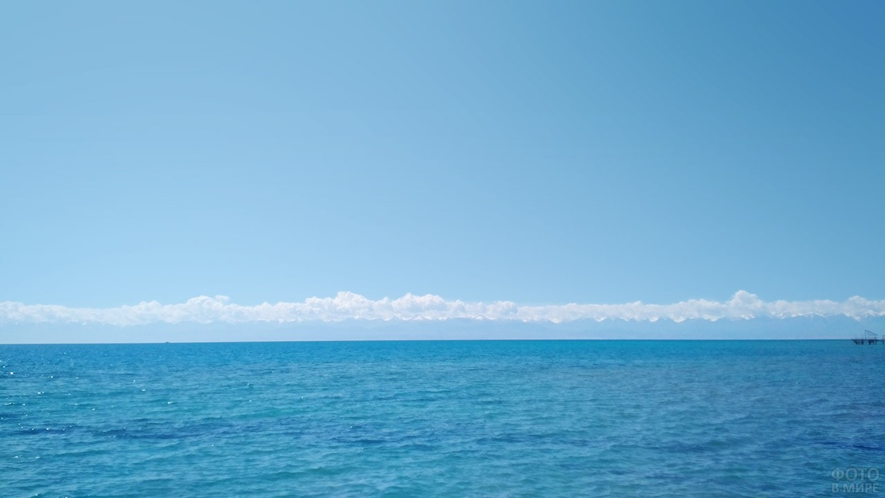 Белые облака над горными вершинами на другом берегу озера